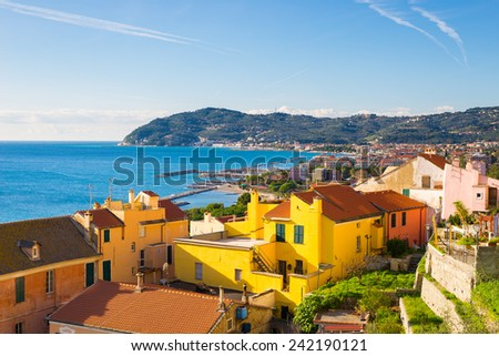 Italian multi colored village on the ligurian sea with beautiful landscape in the background. Morning light, vibrant colors. - stock photo
