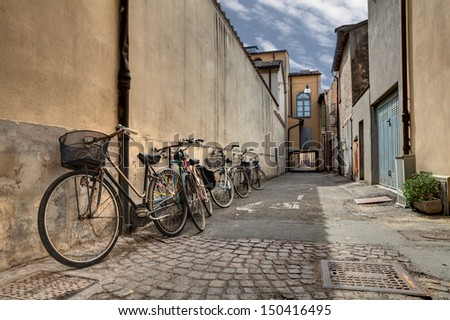 italian narrow street in the decadent old town - bicycles in a grunge dark alley in Italy - stock photo