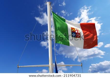 Italian Nautical Flag on Blue Sky / Italian flag with emblem of the four Maritime Republics, Venice, Genoa, Pisa and Amalfi hanging on a ship's mast on blue sky - stock photo