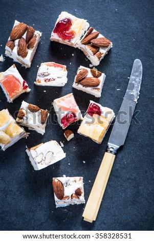 Italian nougat bars cut in pieces on dark slate background - stock photo