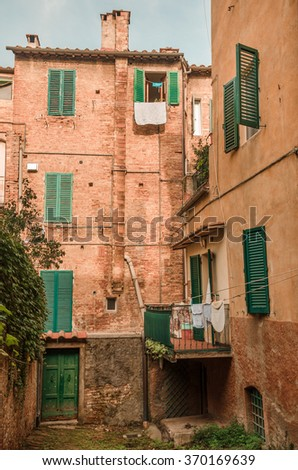 Italian old neighborhood - Residential old stone building with windows and door in green and clothes hanged out at a cul-de-sac in Siena, Tuscany, Italy. - stock photo