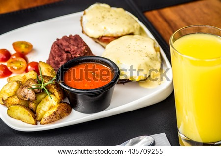 Italian omelette, Frittata, close up, with peperonata, orange juice and coffee, with garden background.