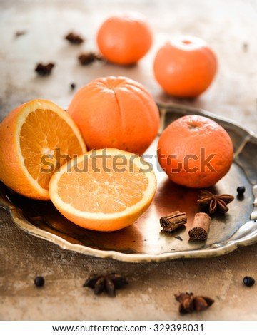 Italian oranges on a metal tray with cinnamon, peppercorns and anise stars.
