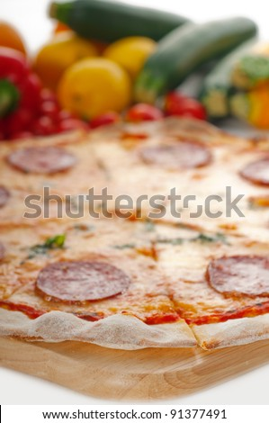 Italian original thin crust pepperoni pizza with fresh vegetables on background - stock photo