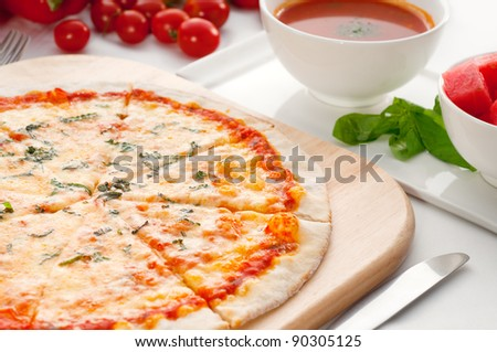 Italian original thin crust pizza Margherita with gazpacho soup and watermelon on side,and vegetables on background - stock photo