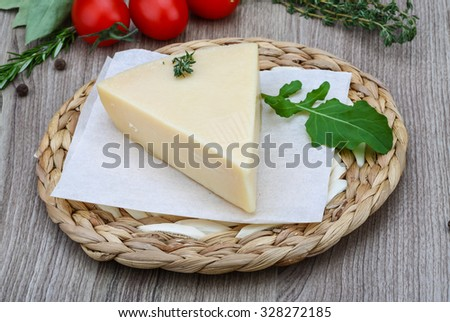 Italian Parmesan cheese with herbs on the wood background - stock photo