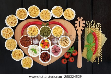Italian pasta and mediterranean food ingredients on a heart shaped board in porcelain bowls over dark wood background. - stock photo