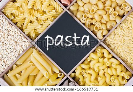 Italian pasta assortment and blackboard for text - stock photo