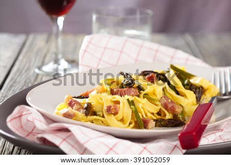 Italian pasta carbonara with asparagus. On wooden rustic table. - stock photo