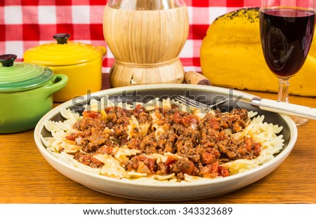 Italian Pasta dinner of bowtie pasta with Chianti Wine based Bolognese Sauce in stereotypical Italian Restaurant.  Straw basket bottle of Chianti Wine. - stock photo