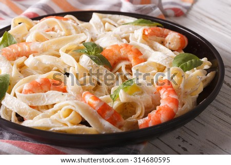 Italian pasta fettuccine in a creamy sauce with shrimp close-up on a plate. horizontal - stock photo