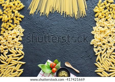 Italian pasta frame. Dry farfalle, penne, rotini, spaghetti over dark background. Basil, pesto, cherry tomato on a vichy towel. - stock photo
