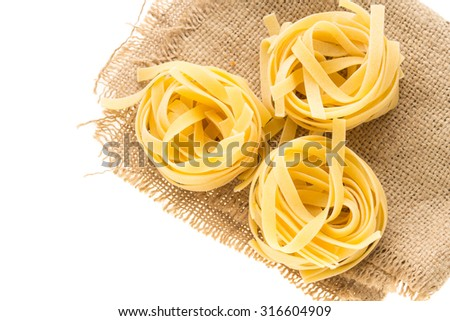 Italian pasta noodle nest on piece of sack on white background - stock photo