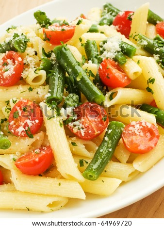 Italian pasta penne with cherry tomatoes and green beans. Shallow dof.