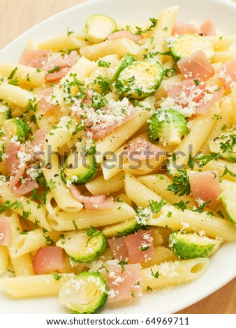 Italian pasta penne with ham and brussels sprouts. Shallow dof. - stock photo