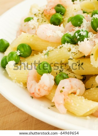 Italian pasta penne with shrimps and green peas. Shallow dof. - stock photo