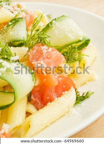 Italian pasta penne with smoked salmon and cucumber. Shallow dof.