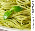 Italian pasta spaghetti with pesto sauce and basil leaf close-up. - stock photo