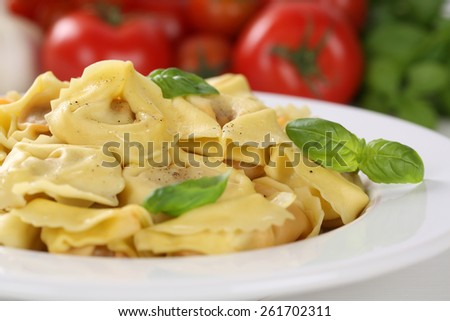 Italian Pasta Tortellini penne noodles meal with tomatoes and basil on plate - stock photo