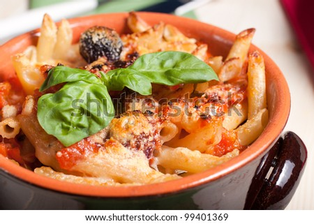 Italian pasta: Very spicy penne gratin baked in earthenware bowl - stock photo