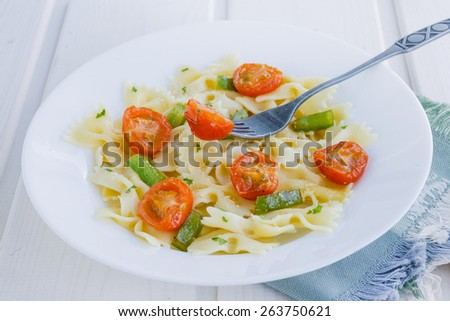 Italian pasta with a tomato cherry on the white table