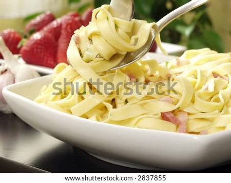 italian pasta with bacon and parsley on decorated table - stock photo