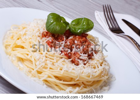 Italian pasta with bolognese sauce and parmesan cheese on the table.