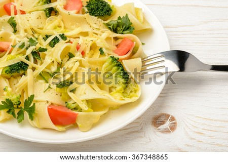 Italian pasta with broccoli, tomatoes and cheese on wooden table.
