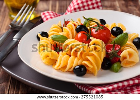 Italian pasta with cherry tomatoes, black olives and basil. - stock photo