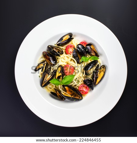 Italian pasta with Gourmet Shellfish, cherry tomato and herbs for a tasty seafood meal over black background, macro - stock photo