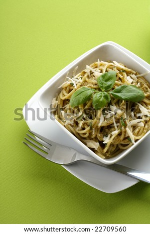 Italian pasta with pesto sauce and parmesan and fork. - stock photo