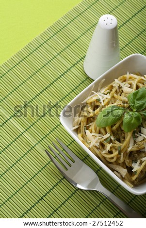Italian pasta with pesto sauce and parmesan and fork.