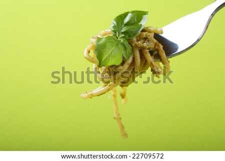 Italian pasta with pesto sauce and parmesan on fork. - stock photo