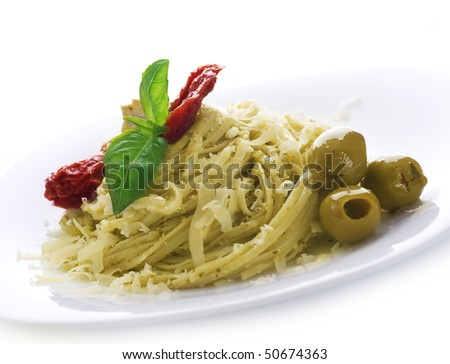 Italian Pasta with Pesto sauce,dried tomato,olives,basil and Parmesan cheese. - stock photo