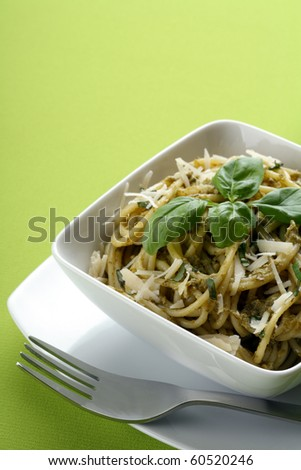 Italian pasta with pesto sause and parmesan and fork. - stock photo
