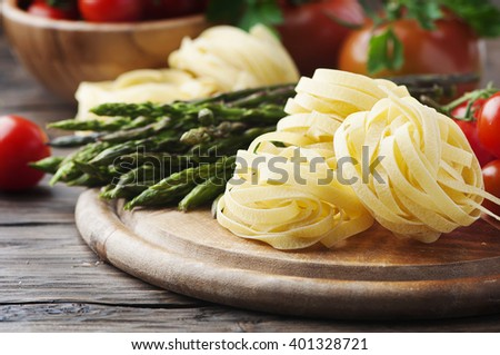 Italian pasta with raw asparagus, selective focus - stock photo