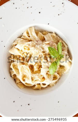 Italian pasta with sauce and parmesan cheese, served on a white plate - stock photo