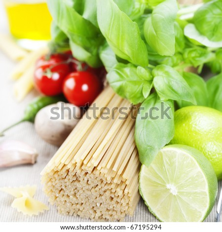 Italian Pasta with tomatoes, mushrooms, olive oil, limes and basil on a white background - stock photo