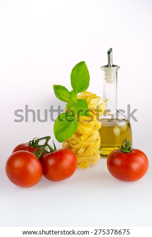Italian Pasta with tomatoes, olive oil and basil on a white background - stock photo