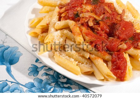 Italian Penne all' Amatriciana, a classic pasta first course from Rome made of tomatoes, guanciale bacon, onions and red hot chili - stock photo