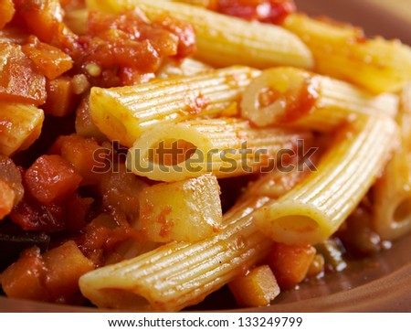 Italian Penne rigate pasta  with  vegetable  tomato sauce  on wooden table - stock photo