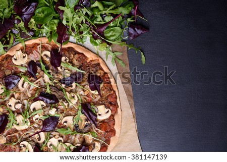 Italian Pizza and spring salad mix with arugula (rucola) on dark wooden background. Overhead view, copy space. - stock photo