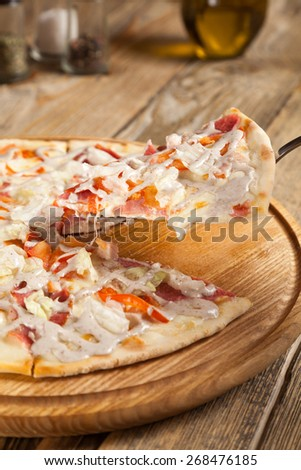 "Italian pizza ""Caesar"" lies on wooden table. On top of the pizza slices bacon, smoked chicken poured white sauce. Nearby are the containers with spices and olive oil. One part is raised on the blade. - stock photo"