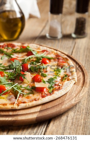 "Italian pizza ""Caprese"" lies on beautiful wooden table. At the top of a pizza cut, baked cherry tomatoes, arugula and parmesan cheese slices. Nearby are the containers with spices and olive oil. - stock photo"