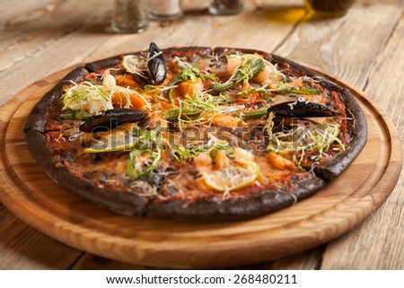 "Italian pizza ""Di Mare"" with black dough and seafood on wooden table. Containers with spices and bottle of olive oil. On top of it lay the shrimp, lemon, arugula, lettuce and open shell with mussels. - stock photo"