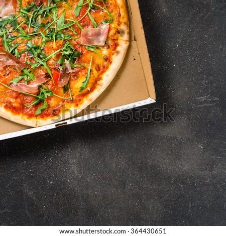 Italian pizza in cardboard box on dark background - stock photo