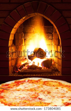 italian pizza margherita and open fire in wood burning oven - stock photo