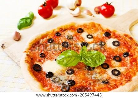 Italian Pizza Margherita with Olives, Mozzarella, Garlic and Basil  - stock photo