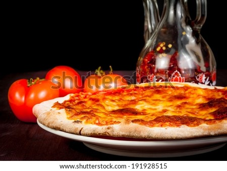 Italian pizza near tomatoes and spicy oil served on wooden table, typical italian pizza - stock photo