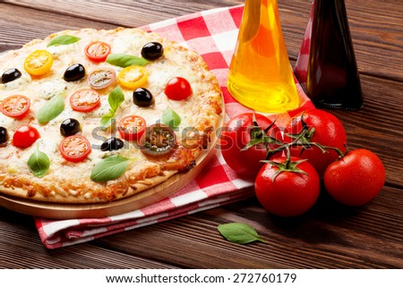Italian pizza with cheese, tomatoes, olives and basil on wooden table - stock photo